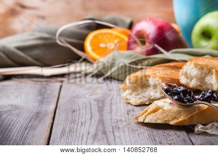 Still life, food and drink concept. French baguette with butter and jam, coffee, fruits for breakfast on a rustic wooden table. Selective focus, copy space background