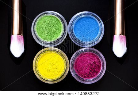 Set of colorful mineral eye shadows on black background
