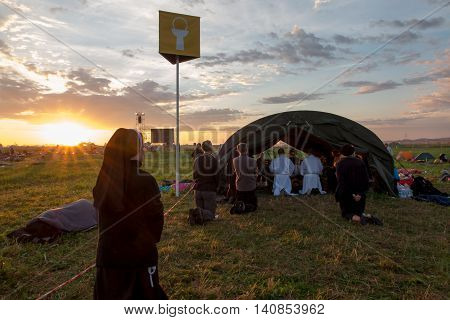 KRAKOW POLAND - JUL 31 2016 World Youth Day and the Catholic youth International Convention July 25-31. Adoration of the Eucharistic Jesus in the rear sectors of the youth on standby at sunrise.