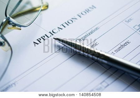 pen and glasses over application form, Completing An Employment Application Form