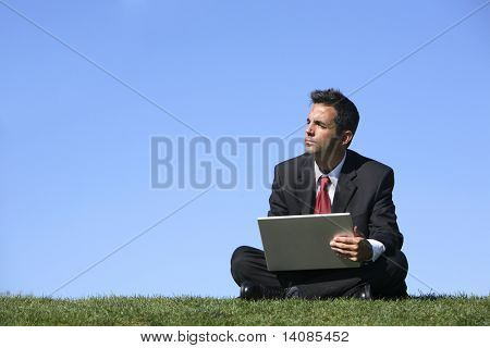 Businessman sitting outdoors with laptop computer