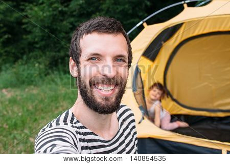 Bearded smiling tourist taking selfie at camping, tent with little girl on background, happy family rest in forest