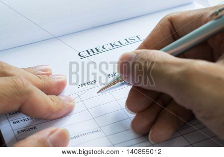 Hand with pen over checklist form, Cropped image of businessman preparing checklist