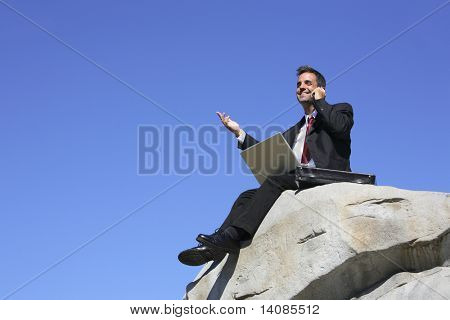 Businessman sitting on top of rock with laptop computer and cell phone