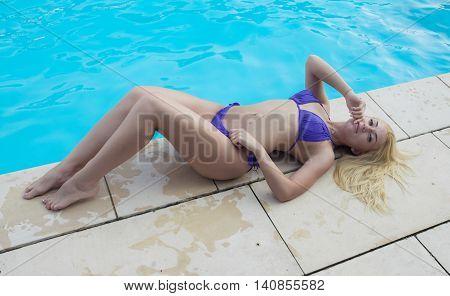 young attractive blonde woman in purple bikini in pool.