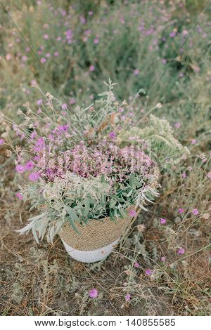 on the field with wild flowers in the grass Wicker basket with immortelles