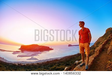 man standing on a cliff against a blue sea at the sunset. Balos beach as background.