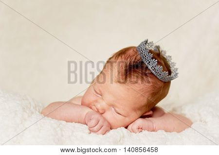 The baby, newly born, lies on the bright plaid and sleeping, handle the person