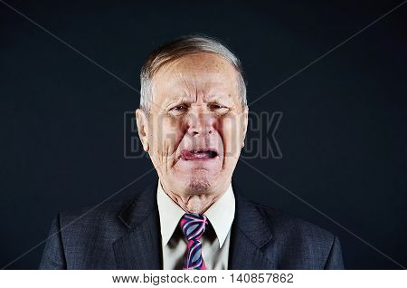 Business man  bad taste, senior man closeup portrait isolated on black background. Emotions, facial expression and people concept