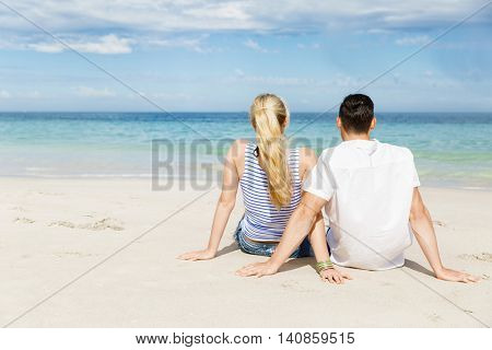 Romantic young couple sitting on the beach