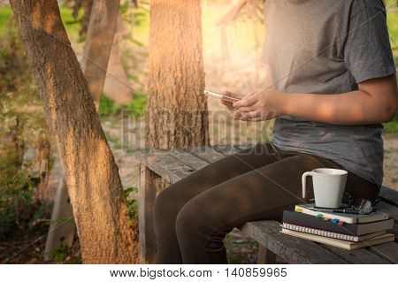 Weekend lifestyle scene of young woman using her smartphone seriously while sitting in outdoor park on wood table in morning time. Freelance business working and phone addiction concept