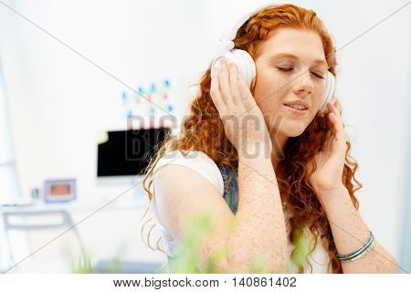Young woman with headphones working in office