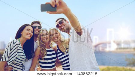 summer holidays, travel, tourism, technology and people concept - group of smiling friends with smartphone photographing and taking selfie over rainbow bridge in tokyo in japan background