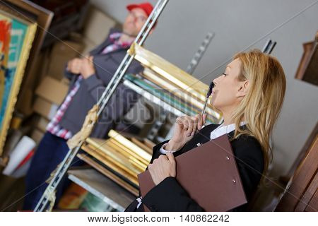 female manager giving orders to subordinate in warehouse