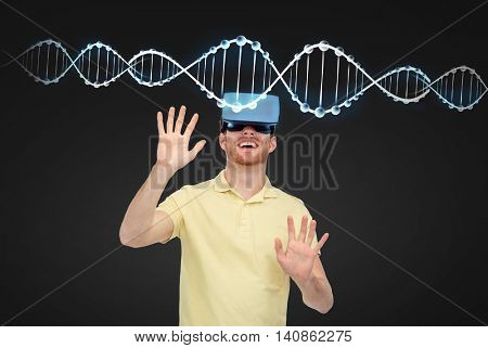 3d technology, virtual reality, entertainment and people concept - happy young man with virtual reality headset or 3d glasses playing game over black background and dns molecule
