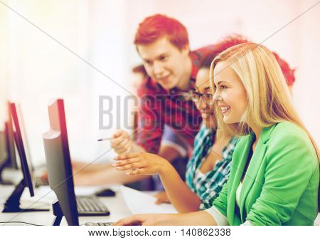 education concept - students with computer studying at school