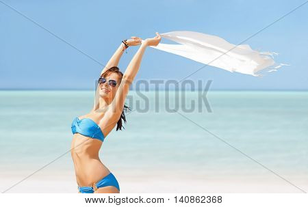 people, summer holidays and vacation concept - happy beautiful woman in bikini and sunglasses with pareo on exotic maldives beach