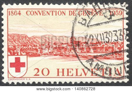 MOSCOW RUSSIA - CIRCA MAY 2016: a post stamp printed in SWITZERLAND shows a view of Geneva dedicated to the 75th Anniversary of the Founding of the International Red Cross Society circa 1939