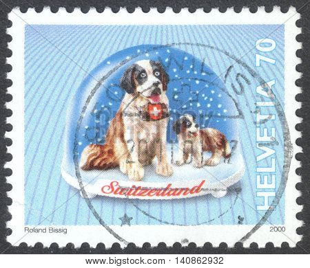 """MOSCOW RUSSIA - CIRCA MAY 2016: a post stamp printed in SWITZERLAND shows a St. Bernard dog the series """"Snow Globes"""" circa 2000"""