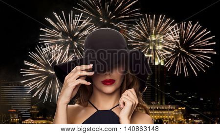 people, luxury and fashion concept - beautiful woman in black hat over night singapore city and firework background