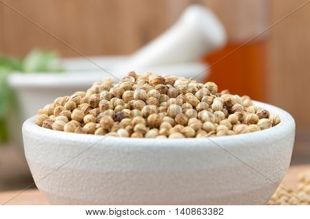 Coriander seeds in a bowl for add Flavor to Your Food on Chopping Wood and Wood background.