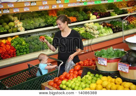 Woman with baby shopping in grocery store