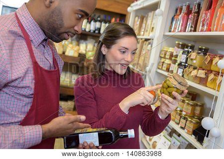 salesman serving female customer purchasing in supermarket