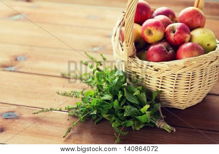 gardening, season, autumn, herbs and fruits concept - close up of wicker basket with ripe red apples and melissa bunch on wooden table