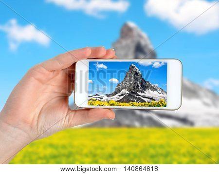 Person is taking photo mountain landscape  with a smartphone.