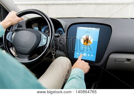 transport, modern technology and people concept - close up of man driving car with music player on board computer screen