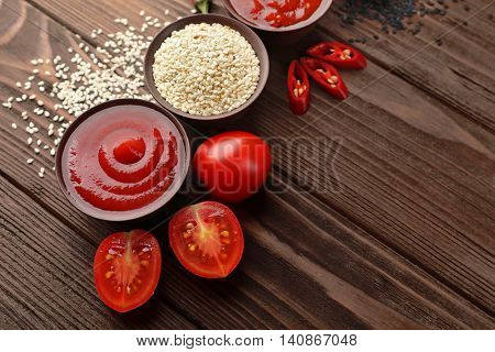 Fresh condiments and sauces on wooden background
