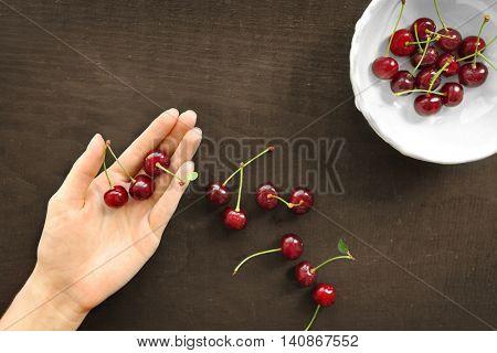 Human hand holding cherries, top view