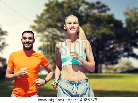 fitness, sport, exercising and healthy lifestyle concept - smiling couple running or jogging over summer park background