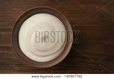 Bowl of fresh cream on wooden background