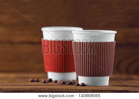 Paper cups of coffee on wooden background