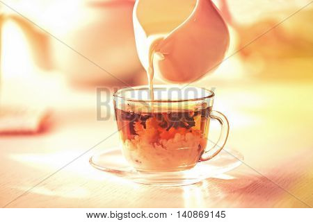 Pouring milk in tea on table