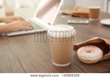 Paper cup of coffee on wooden table closeup