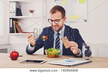 Man has healthy business lunch in modern office interior. Young handsome businessman in eyeglasses at working place, looking at plate with vegetable salad in bowl, diet and eating right concept.