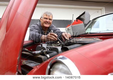 Senior man working on classic car