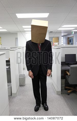 Businessman in office with bag on head