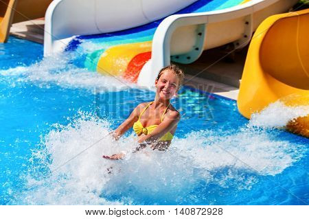 Child on water slide at water park . Child girl in water splashes.
