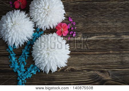 Bouquet of white chrysanthemums decorated with sea salt on a wooden background. Floral background