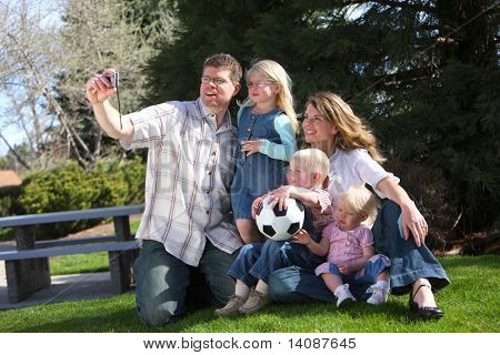 Family with camera taking a self portrait at park