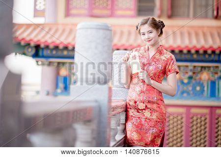 The Asian Woman In Chinese Dress Holding Couplet 'lucrative.' (chinese Word) With Chinese Temple Bac