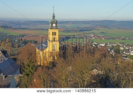 View of the Ore Mountains in Saxony, Germany; meadows, fields, forests, villages and blue sky; in the foreground the town Augustusburg with the town church and houses; landscape in late autumn, bird's-eye view