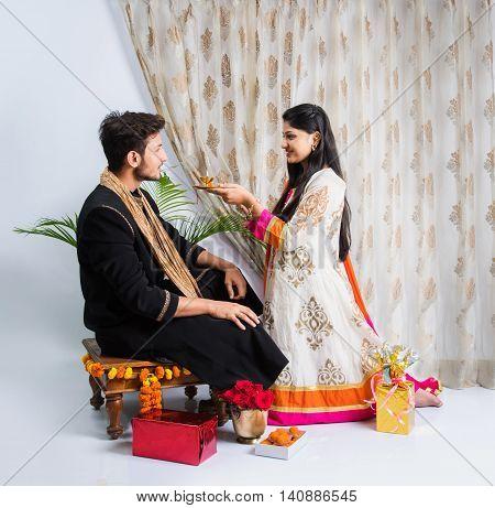 indian sister applying tika on brother's forehead, enjoying and celebrating Raksha Bandhan festival