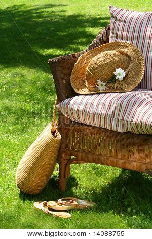Gras Rasen mit einem Weide-Stuhl wartet auf jemanden zum Entspannen an einem heißen Sommertag