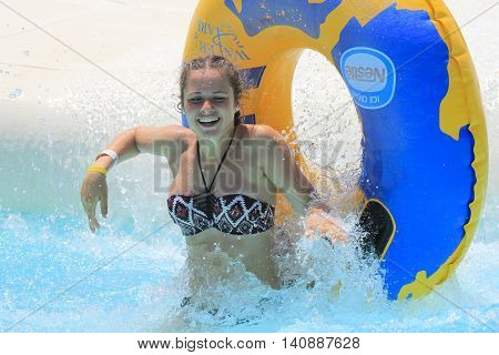 Rhodes Greece-July 30 2016: The girl after rafting slide in the Water park.Rafting slide is one of many popular game for adults and children in park.Water Park is located on the island of Rhodes in Greece and one of the most largest in Europe