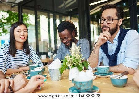 Young people drinking coffee at coffeeshop outdoors