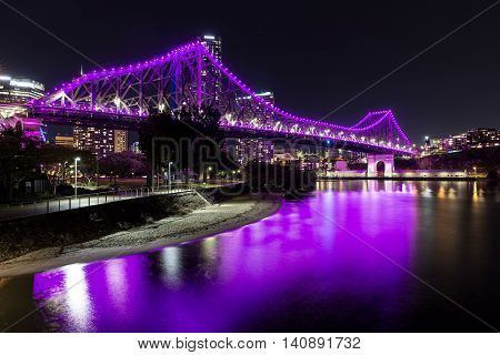 Brisbane Story Bridge (magenta) and beach by night